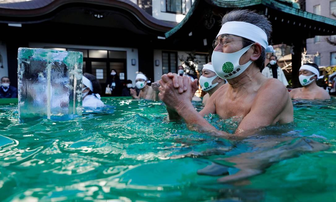 Banho gelado durante uma cerimônia para purificar suas almas e desejam superar a pandemia no santuário Teppozu Inari em Tóquio, Japão Foto: KIM KYUNG-HOON / REUTERS