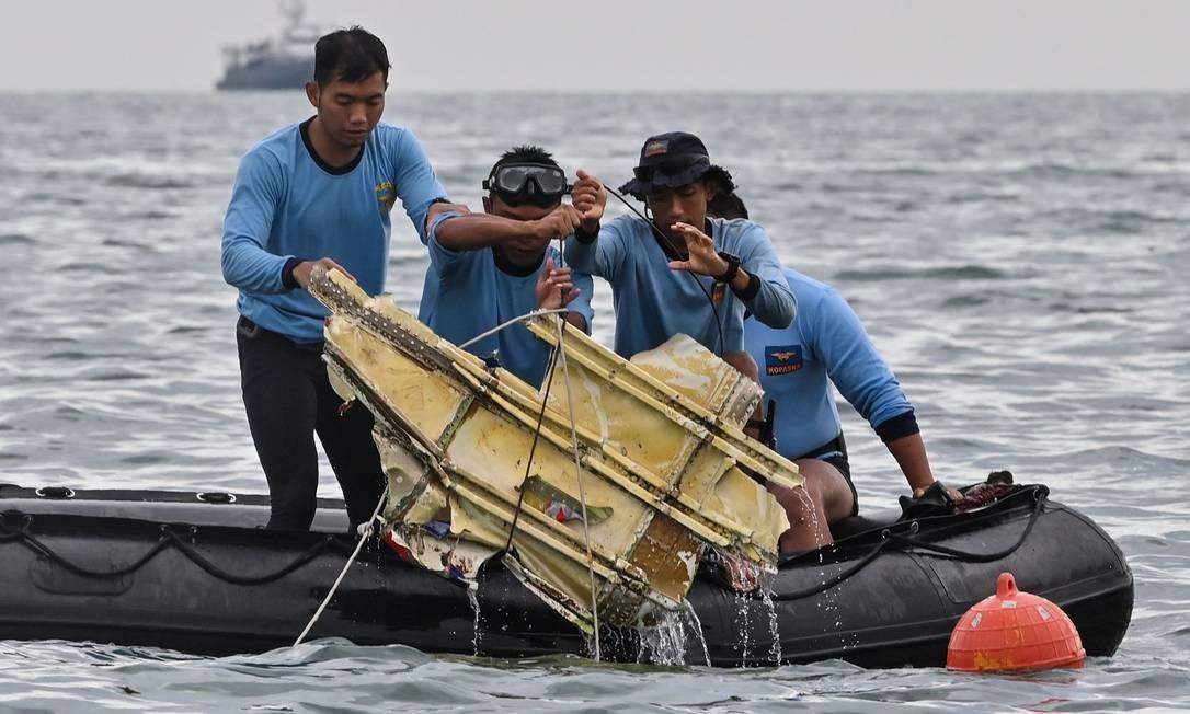 Mergulhadores da Marinha da Indonésia seguram destroços do voo SJY182 da Sriwijaya Air durante uma operação de busca e resgate no mar perto da ilha de Lancang Foto: ADEK BERRY / AFP