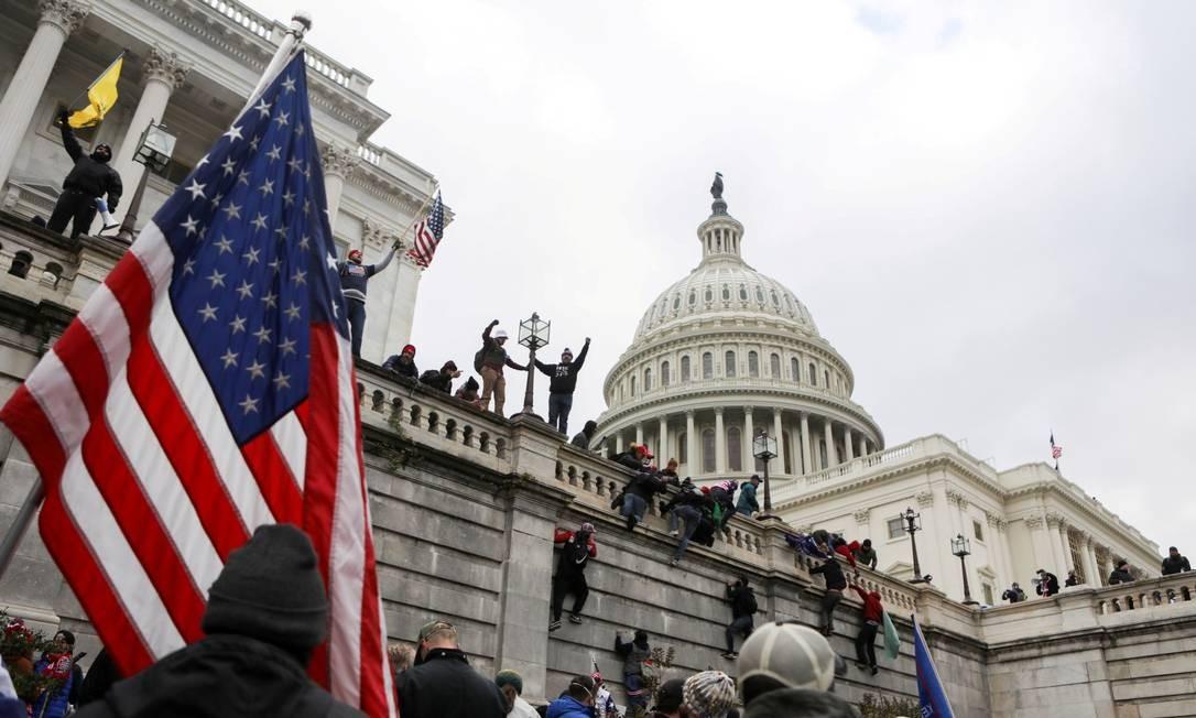 Apoiadores do presidente Donald Trump escalam paredes no Capitólio dos EUA durante ato para impedir a certificação da vitória de Joe Biden, no último dia 6 Foto: JIM URQUHART / REUTERS