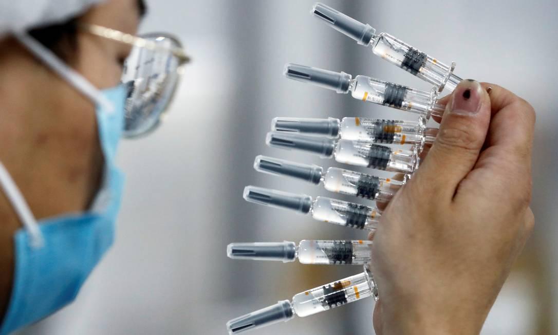 Funcionário realiza teste de qualidade em local de embalamento da Sinovac Biotech,fabricante da CoronaVac Foto: THOMAS PETER / REUTERS