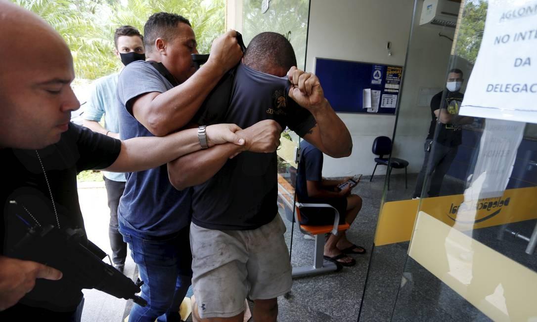 O capitão do Corpo de Bombeiros João Maurício chega à delegacia do Recreio com o rosto coberto Foto: Fabiano Rocha / Agência O Globo