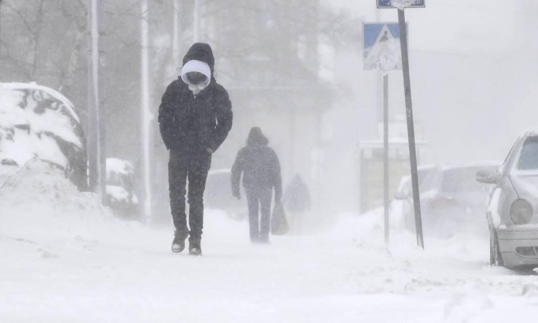 TOPSHOT - Os pedestres abrem caminho por uma espessa camada de neve que cobre as ruas de Helsinque, Finlândia, em 12 de janeiro de 2021. - A forte nevasca deve continuar até quarta-feira, 13 de janeiro de 2021 no sul da Finlândia. As condições de condução são más devido à neve e às estradas escorregadias. (Foto de Vesa Moilanen / Lehtikuva / AFP) / Finlândia OUT Foto: VESA MOILANEN / AFP
