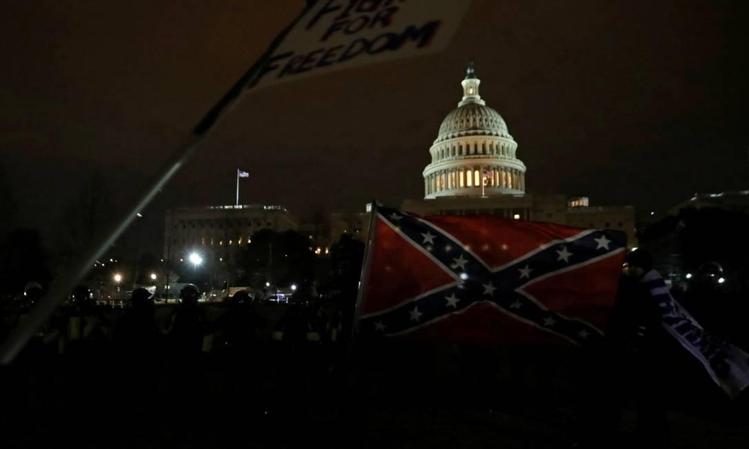Manifestante pró-Trump carregam bandeira dos estados confederados, com o Capitólio ao fundo Foto: LEAH MILLIS / REUTERS / 6-1-21