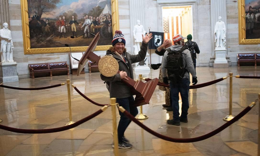ADAM CHRISTIAN JOHNSON, 36 anos, residente da Flórida, preso na noite de sexta-feira (8). Durante o tumulto no Capitólio, Adam foi flagrado carregando o púlpito da presidente da Câmara dos EUA, Nancy Pelosi Foto: WIN MCNAMEE / AFP
