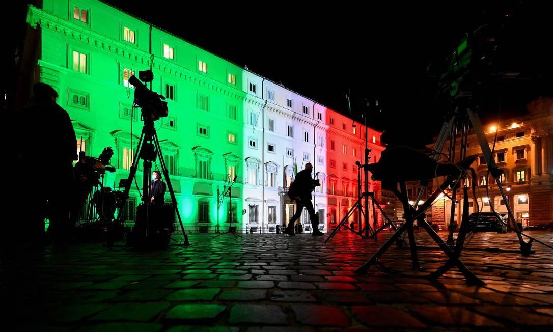 Jornalistas aguardam fora do Palazzo Chigi, a sede do governo italiano, iluminado com as cores da bandeira do país, o governo discutir um pacote de gastos de recuperação do coronavírus de 220 bilhões de euros Foto: VINCENZO PINTO / AFP/12-01-2021