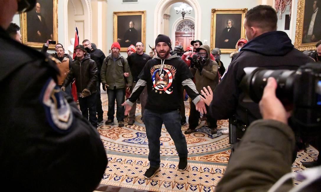 DOUG JENSEN, 41 anos, morador do estado de Iowa, foi preso pelo FBI na madrugada de sábado. Doug foi reconhecido em imagem que se tornou icônica durante o motim no Capitólio. É ele o homem que, vestindo um boné de tricô e uma camiseta da QAnon com uma águia, aparece com os braços abertos enfrentando seguranças do Congresso Foto: MIKE THEILER / REUTERS