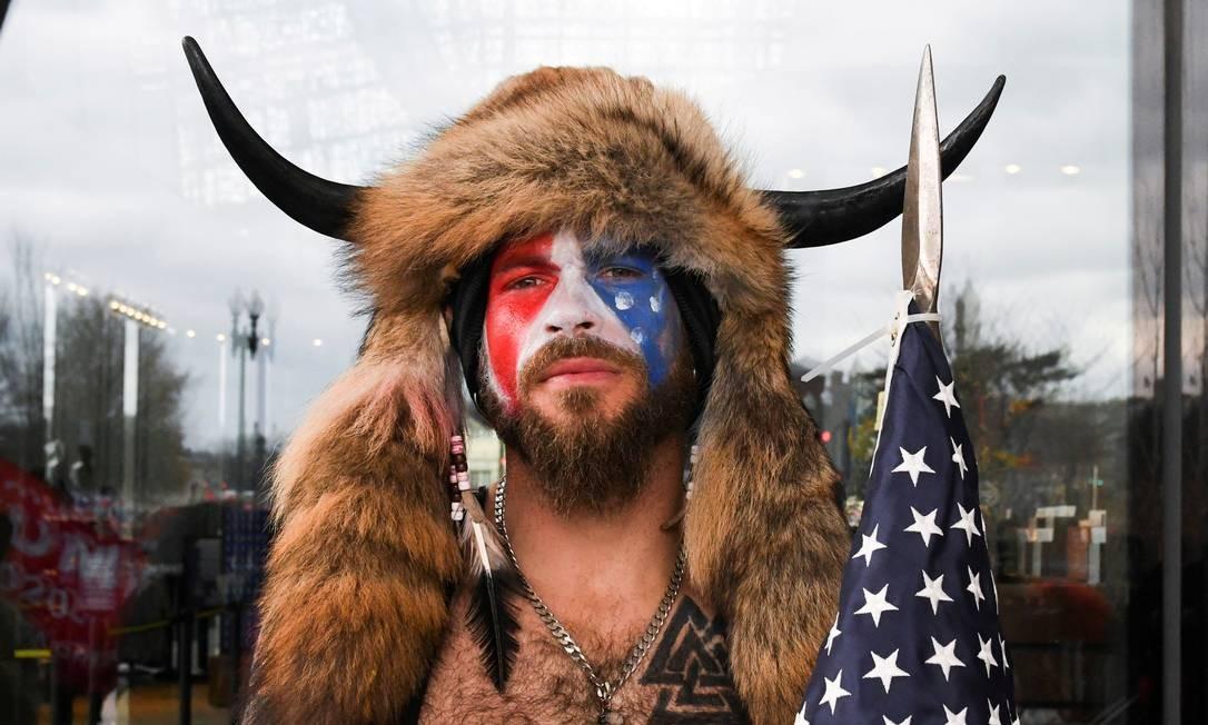 JACOB ANTHONY CHANSLEY. Também conhecido como Jake Angeli, 32, do Arizona, foi preso no final da tarde de sábado (9). Considerado o personagem que simbolizou a invasão ao Capitólio por causa de sua caracterização, o radical trumpista se apresentou voluntariamente às autoridades em Washington. Durante a invasão, Jake, que é adepto da teoria conspiratória QAnon, tinha o rosto pintado com as cores da bandeira dos EUA e vestia um chapéu de pele com chifres Foto: STEPHANIE KEITH / REUTERS