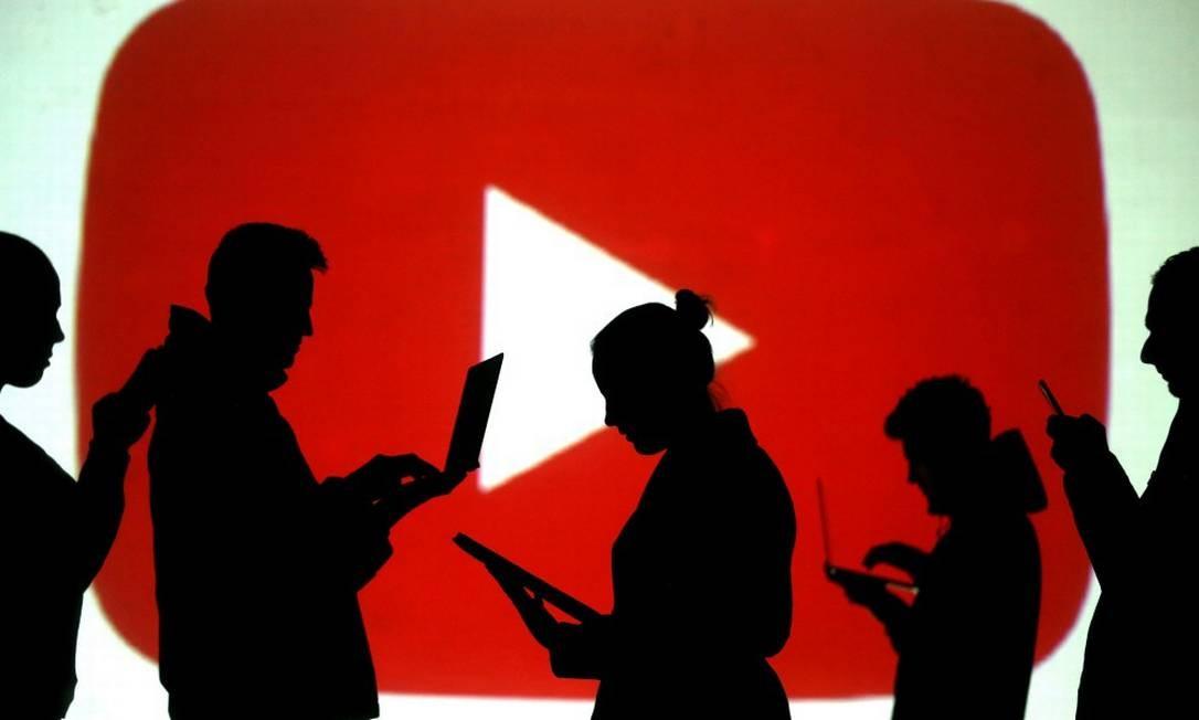 Pessoas usam dispositivos móveis diante de uma tela com a logo do YouTube Foto: Dado Ruvic / REUTERS / 28-3-18