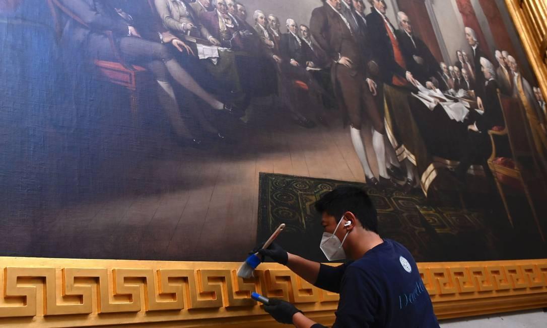 Preservacionista usa pincel para limpar a moldura de ouro em quadro da Rotunda do Capitólio dos EUA Foto: ANDREW CABALLERO-REYNOLDS / AFP