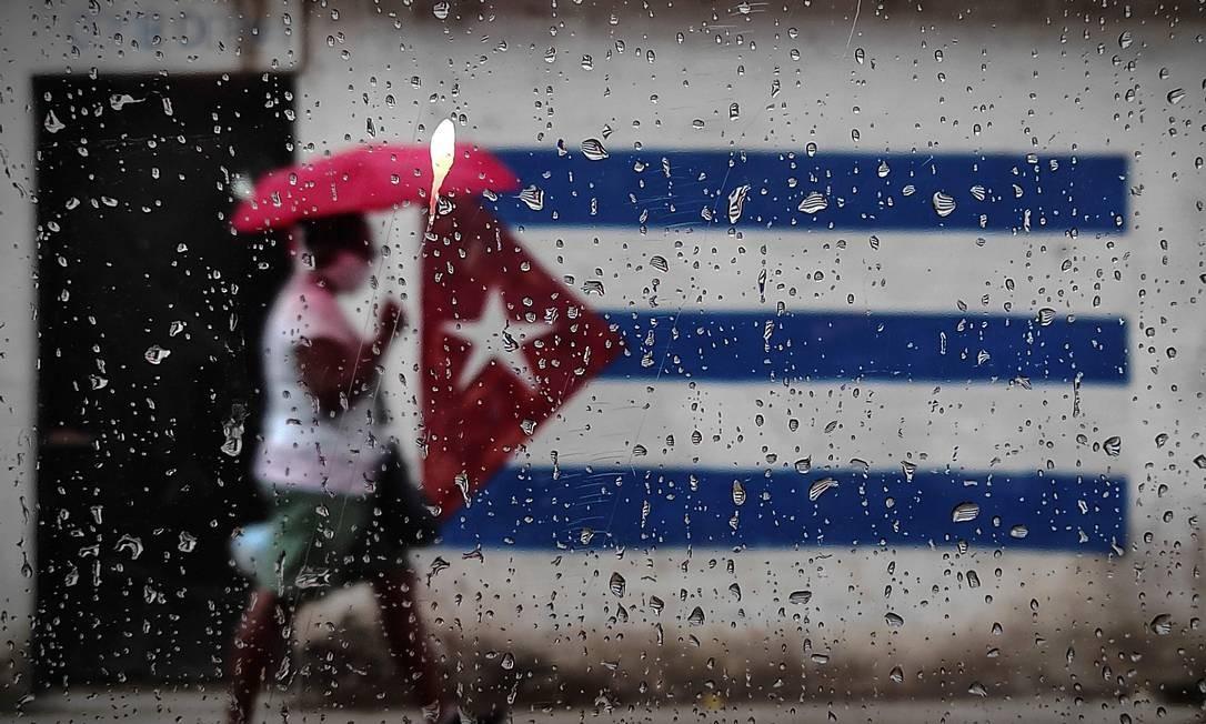 """Mulher caminha perto de um grafite com a bandeira cubana em Havana. O ministro das Relações Exteriores de Cuba, Bruno Rodriguez, criticou na segunda-feira o governo do presidente dos Estados Unidos, Donald Trump, por """"oportunismo político"""" por colocar o país de volta em um lista negra de patrocinadores estatais do terrorismo Foto: YAMIL LAGE / AFP"""