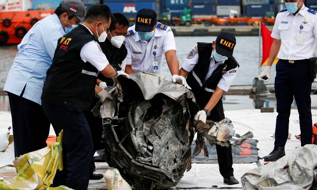 Oficiais da Comissão Nacional de Segurança no Transporte (KNKT) inspecionam os destroços do voo SJ-182 da Sriwijaya Air, que caiu no mar, no porto de Tanjung Priok em Jacarta, Indonésia Foto: WILLY KURNIAWAN / REUTERS