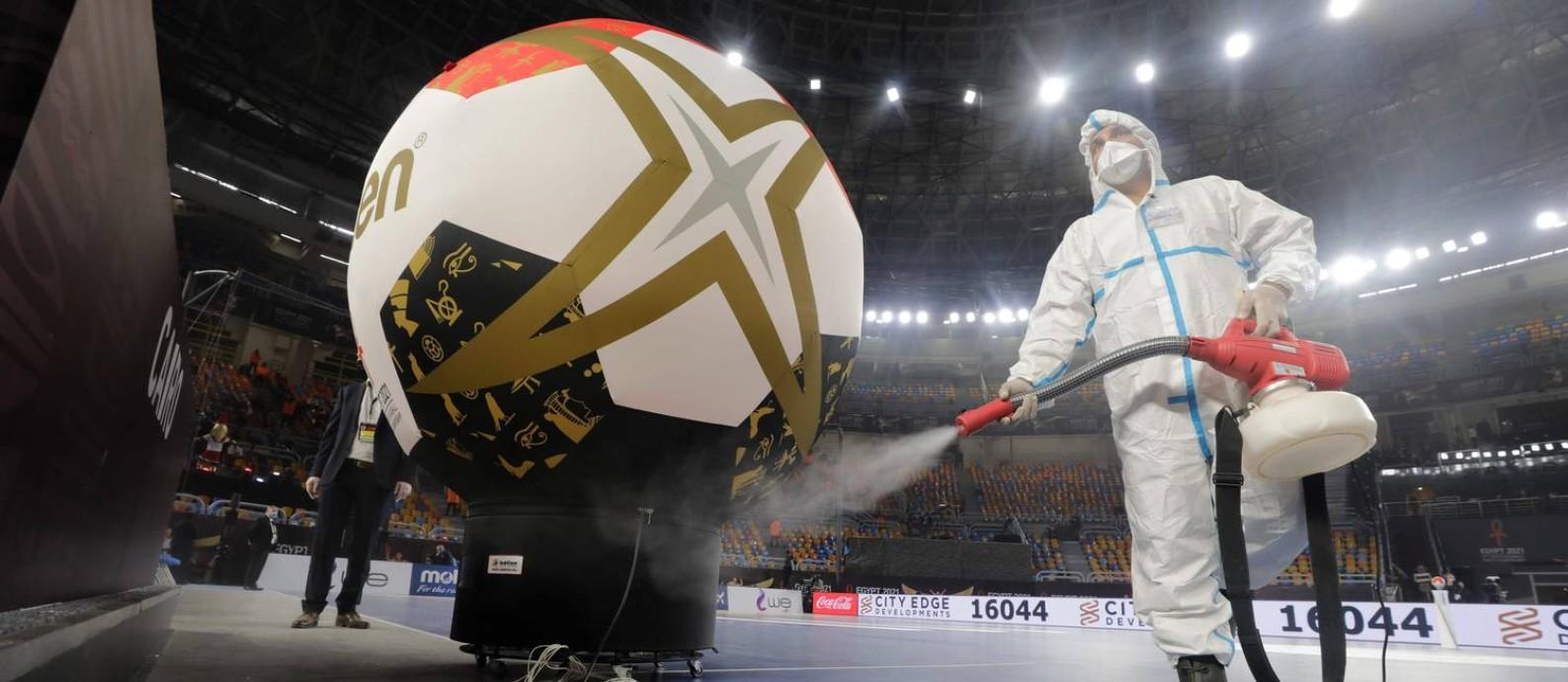 Funcionário desinfeta a quadra da partida de abertura do Mundial de Handebol masculino, entre Egito e Chile, no Cairo Foto: MOHAMED ABD EL GHANY / AFP