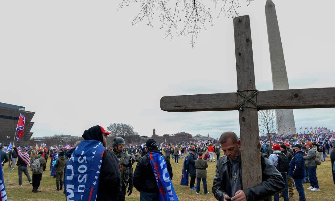 Homem segura cruz durante protesto contra a certificação dos resultados da eleição presidencial dos EUA, no dia 6 de janeiro Foto: JOSEPH PREZIOSO / AFP