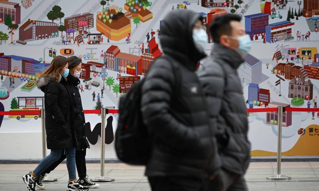Pedestres caminham de máscara em Pequim, na China Foto: WANG ZHAO / AFP