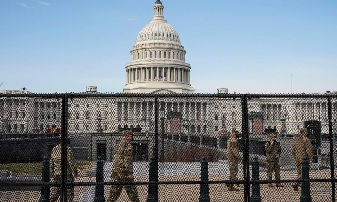 Soldados da Guarda Nacional a postos na frente do Capitólio, protegido por uma cerca Foto: JOSHUA ROBERTS / REUTERS