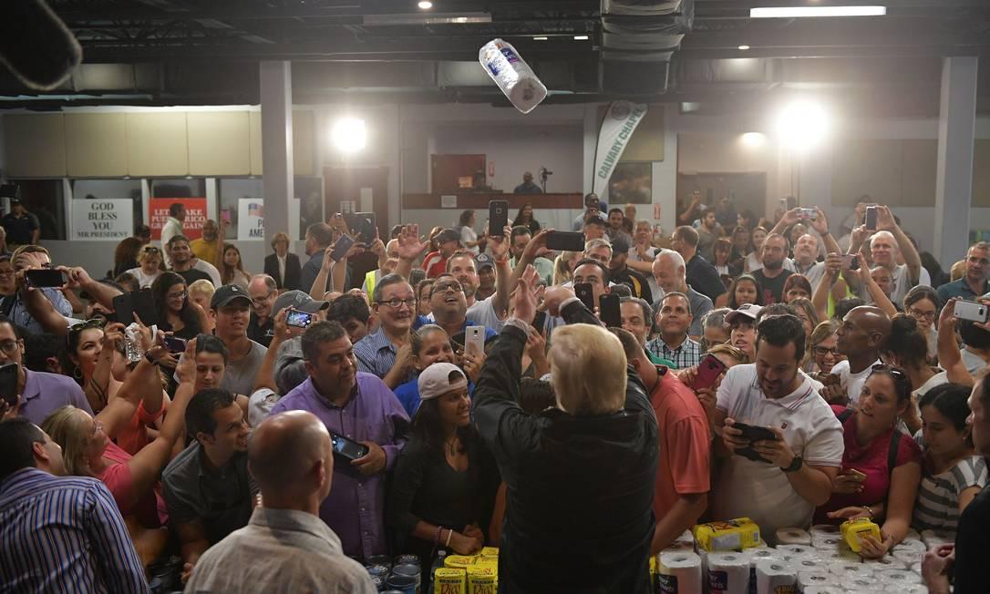Trump, joga um rolo de papel toalha ao visitar a Capela da Cavalaria, em Guaynabo, Porto Rico, em outubro de 2017. Quase duas semanas depois que o furacão Maria atingiu o território dos Estados Unidos, muitas das ilhas continuavam sem comida e sem acesso para energia ou água potável Foto: MANDEL NGAN / AFP - 03/10/2017