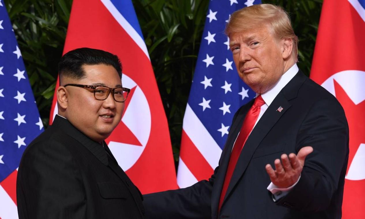Trump acena ao se encontrar com o líder da Coreia do Norte, Kim Jong-Un no início de sua cúpula histórica EUA-Coreia do Norte, no Capella Hotel, na ilha de Sentosa, em Cingapura, em junho de 2018. Trump e Kim Jong-Un se tornaram os primeiros líderes dos Estados Unidos e da Coreia do Norte a se reunir, apertar as mãos e negociar para encerrar um impasse nuclear de décadas Foto: SAUL LOEB / AFP - 12/06/2018