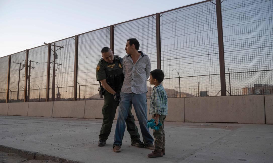José, 27 anos, com seu filho José Daniel, 6, é revistado pelo agente da Alfândega e Proteção de Fronteiras dos EUA, Frank Pino, em maio de 2019, em El Paso, Texas. Pai e filho passaram um mês viajando pela Guatemala através do México. À época, cerca de 1.100 migrantes da América Central e de outros países tentavam cruzar para o setor de fronteira de El Paso a cada dia, refletindo uma das maiores crise de imigração da história Foto: PAUL RATJE / AFP - 16/05/2019