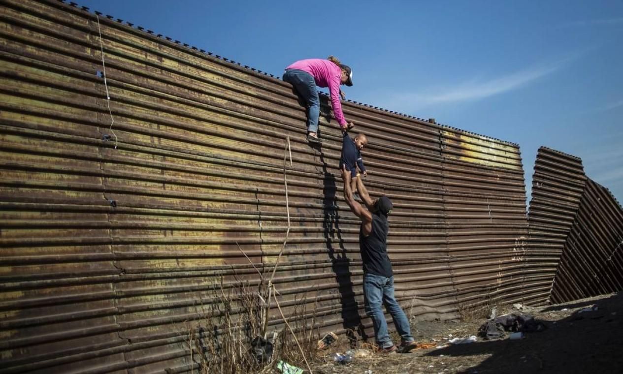 Um grupo de imigrantes centro-americanos escalam a cerca da fronteira entre o México e os Estados Unidos, perto do cruzamento da fronteira de El Chaparral, em Tijuana, estado de Baixa Califórnia, México, em novembro de 2018 Foto: PEDRO PARDO / AFP - 25/11/2018