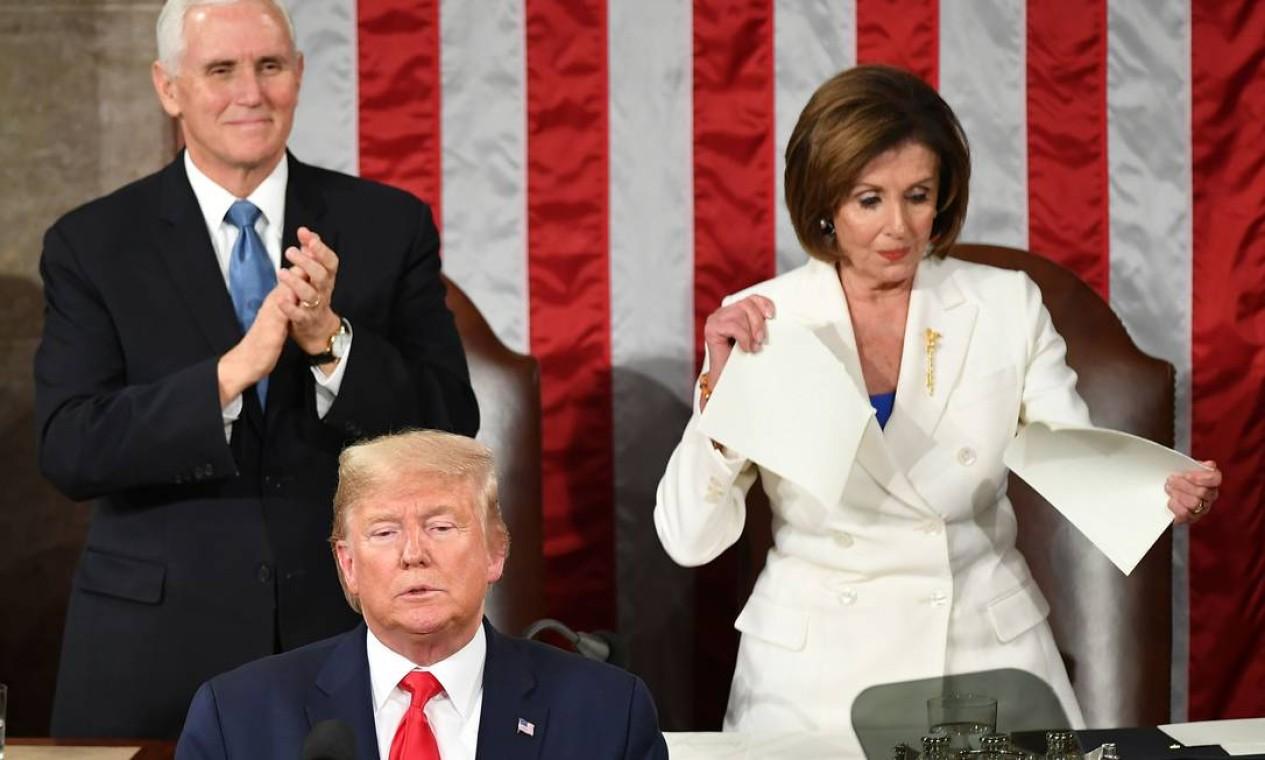 O vice-presidente dos Estados Unidos, Mike Pence, aplaude enquanto a presidente da Câmara e lider dos democratas, Nancy Pelosi, rasga uma cópia do discurso de Trump após a fala do presidente americano durante o tradicional discurso anual no Congresso, em Washington, em fevereiro de 2020 Foto: MANDEL NGAN / AFP - 04/02/2020