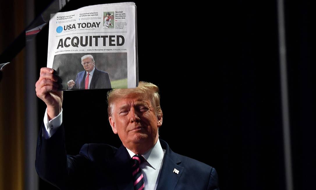 """Trump mostra um jornal que exibe a manchete """"Absolvido"""" quando chega para falar no 68º Café da Manhã de Oração Nacional, em fevereiro de 2020. O presidente disse que sofreu uma """"terrível provação"""" durante seu impeachment Foto: NICHOLAS KAMM / AFP - 06/02/2020"""
