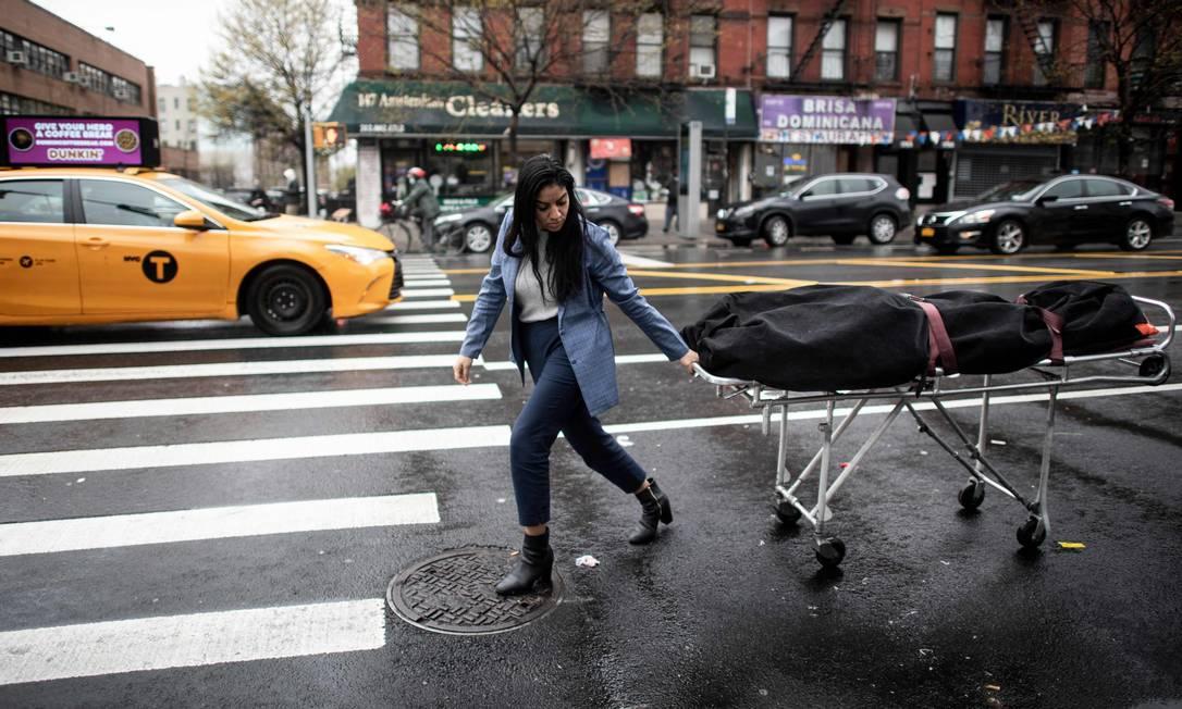Alisha Narvaez, gerente de uma funerária, transporta um corpo no bairro de Harlem, na cidade de Nova York, em abril de 2020. Empresas do setor ficaram sobrecarregadas durante os meses de pico de mortes pelo coronavírus em Nova York Foto: JOHANNES EISELE / AFP - 24/04/2020