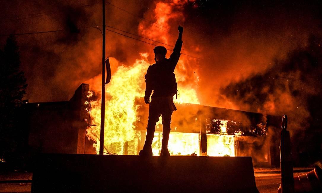 Um manifestante reage em frente a um prédio em chamas durante uma manifestação em Minneapolis, Minnesota, em 29 de maio. Protestos antirracistas eclodiram pelos EUA após a morte de George Floyd. Movimento negro e contra a violência policial pautou a disputa eleitoral Foto: CHANDAN KHANNA / AFP - 29/05/2020