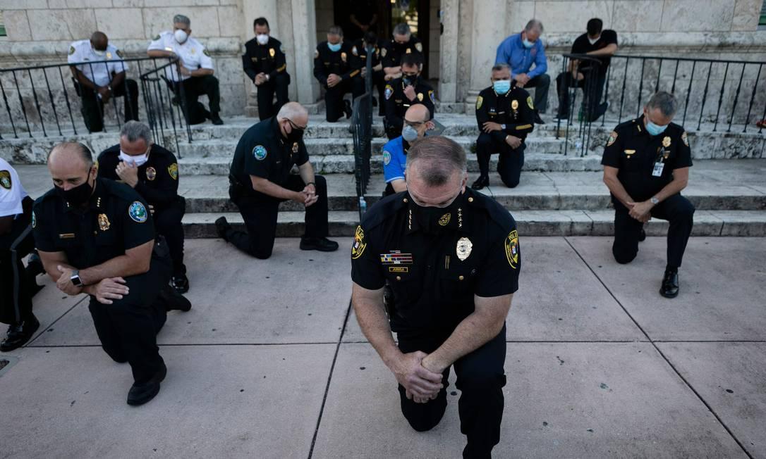 Policiais se ajoelham durante um protesto em Coral Gables, Flórida, em 30 de maio, em resposta à morte de George Floyd. Confrontos estouraram nas principais cidades, com manifestantes furiosos que ignoravam as advertências de Trump de que seu governo impediria protestos violentos sobre a brutalidade policial Foto: EVA MARIE UZCATEGUI / AFP - 30/05/2020