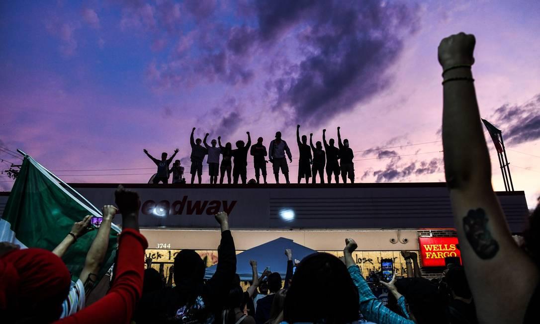 As pessoas levantam as mãos e gritam slogans enquanto protestam no memorial improvisado em homenagem a George Floyd, em 2 de junho Foto: CHANDAN KHANNA / AFP - 02/06/2020