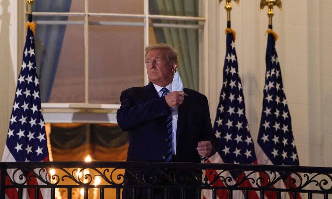 Donald Trump tira a máscara ao chegar à Casa Branca depois de retornar do Walter Reed Medical Center, onde se submeteu a tratamento para Covid-19, em Washington Foto: NICHOLAS KAMM / AFP - 05/10/2020