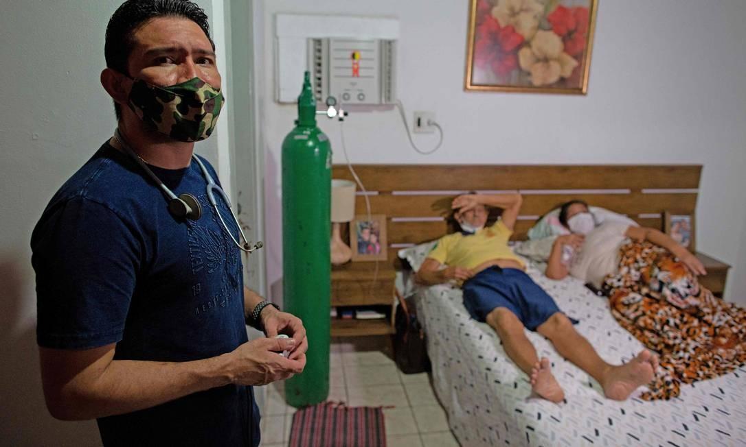 """O médico Marcos Fonseca Barbosa é visto ao lado de seus pais, Glauco Rego Lima, 72, e Ruth Fonesca, 56, ambos infectados com o novo coronavírus. Desesperado e desamparado, o médico optou por tratar a mãe, que apresenta quadro grave da Covid, em casa, já que não conseguiu vaga para interná-la. """"Tive medo que ela morresse nos meus braços"""", confessa Foto: MICHAEL DANTAS / AFP - 12/01/2021"""