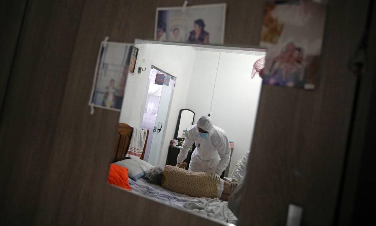 Agente municipal de saúde examina o corpo de Lacy Braga de Oliveira, que faleceu em casa, aos 84 anos, com sintomas da COVID-19. A escalada de novos casos da doença em Manaus fez crescer o número de registro de mortes em domicílio Foto: BRUNO KELLY / REUTERS - 11/01/2021