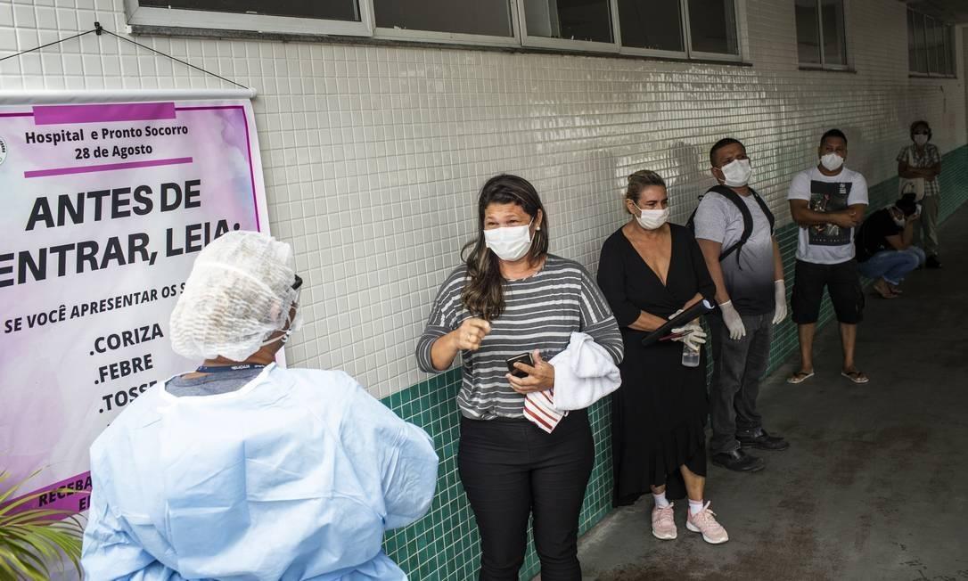 Pessoas com sintomas da Covid-19 aguardam em fila para atendimento no Hospital e Pronto Socorro 28 de Agosto, em Manaus Foto: Raphael Alves / Agência O Globo