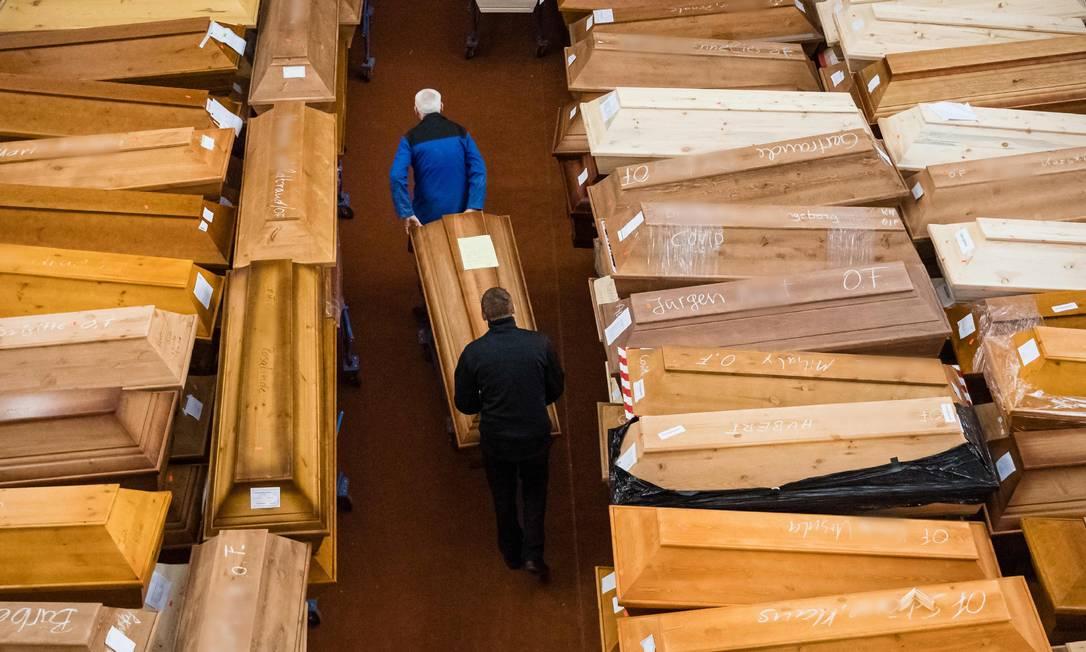 """Funcionários armazenam caixões, alguns marcados com """"risco de infecção"""", enquanto outros têm a palavra """"corona"""" rabiscada em giz, no salão de luto do crematório em Meissen, leste da Alemanha, em meio à nova pandemia de coronavírus Foto: JENS SCHLUETER / AFP/13-01-2021"""