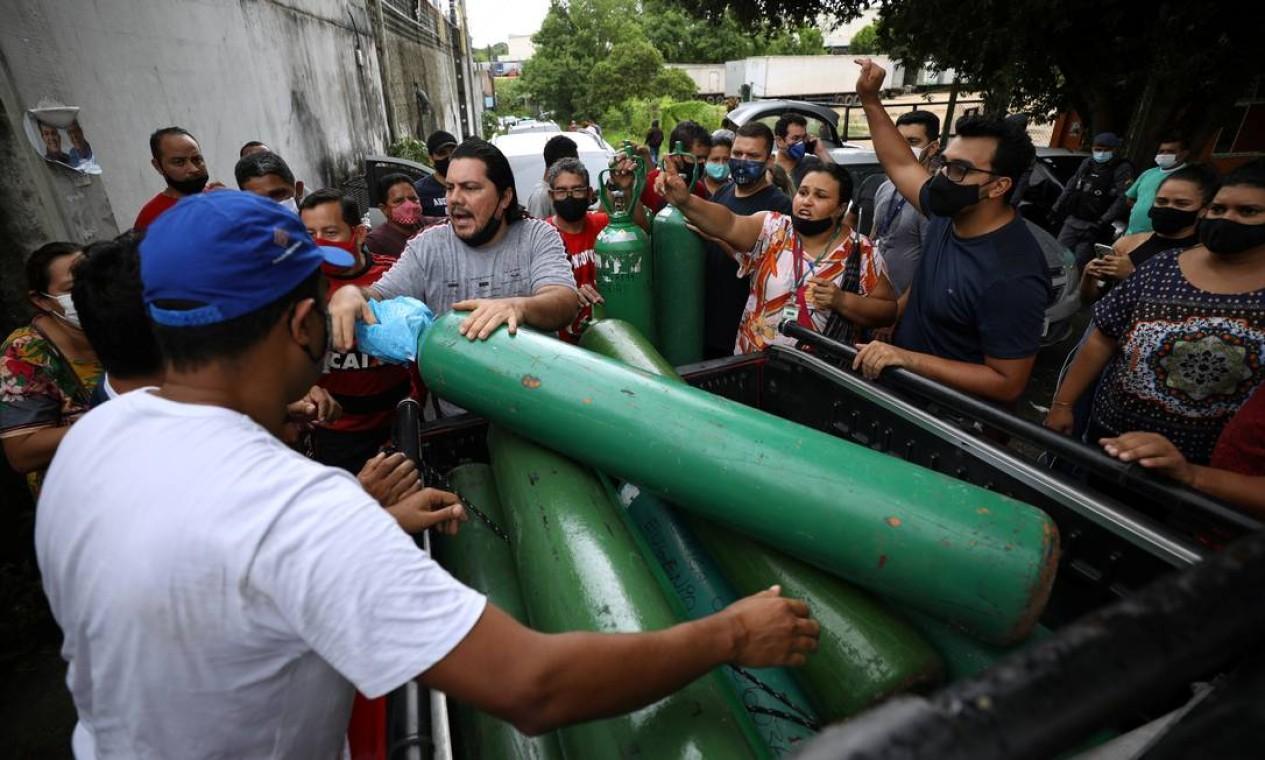 Parentes de pacientes hospitalizados ou recebendo assistência médica em casa, a diagnosticada com COVID-19, disputam para comprar oxigênio e encher botijões em uma empresa privada em Manaus Foto: BRUNO KELLY / REUTERS - - 15/01/2021