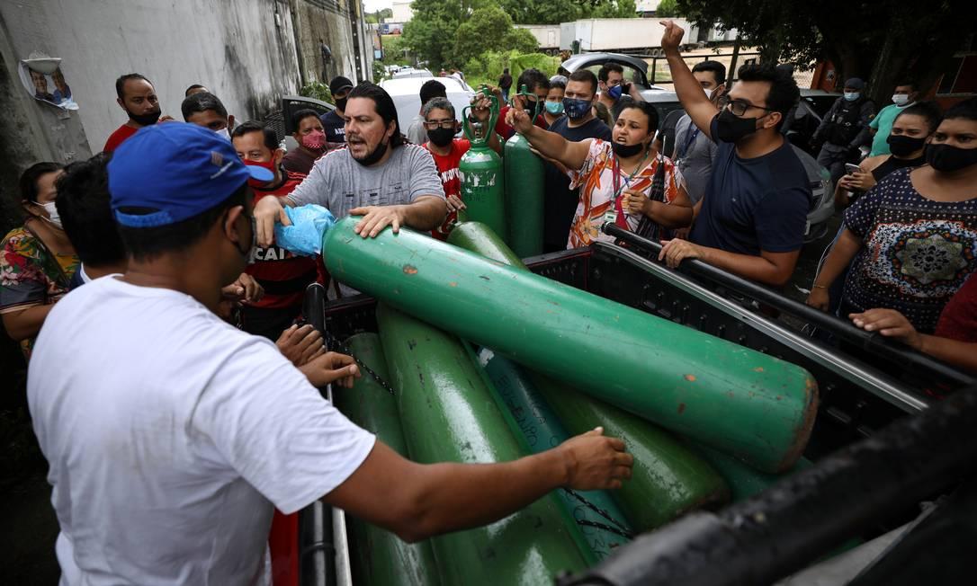 Parentes de pacientes hospitalizados ou recebendo assistência médica em casa, a maioria com COVID-19, se reúnem para comprar oxigênio e encher botijões em uma empresa privada em Manaus Foto: BRUNO KELLY / REUTERS