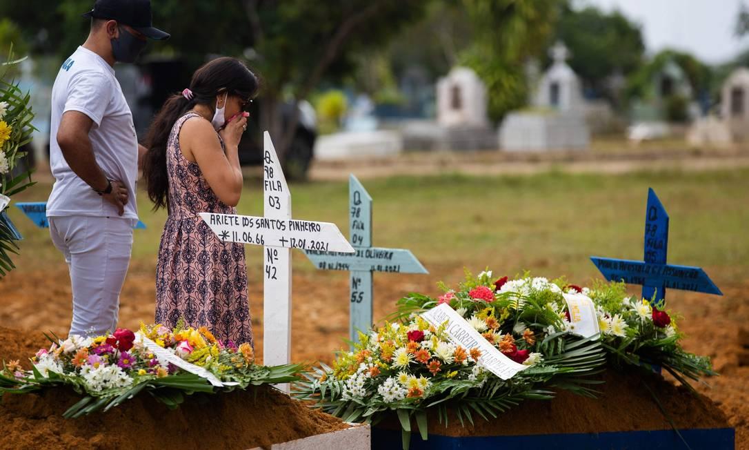 Familiares assistem ao funeral de uma vítima do Covid-19 no cemitério Nossa Senhora Aparecida em Manaus Foto: MICHAEL DANTAS/AFP
