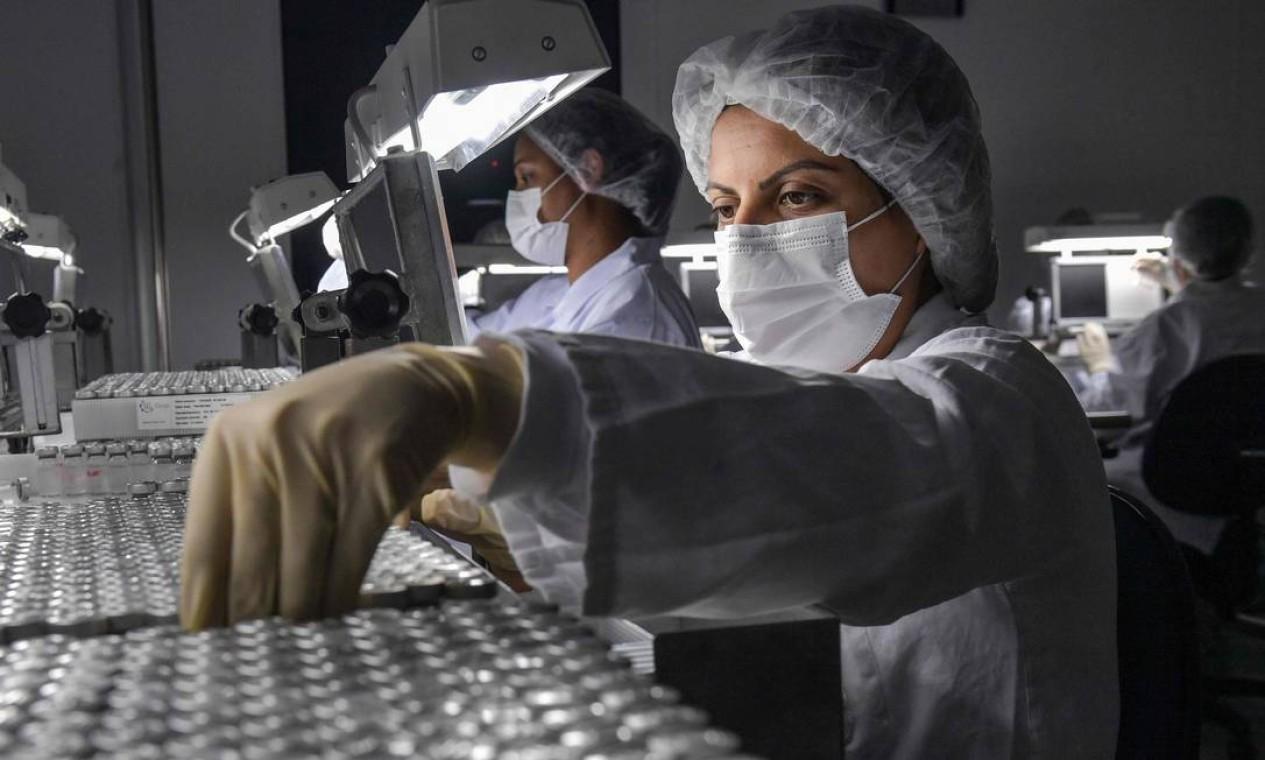 Funcionários trabalham na linha de produção da Coronavac, vacina da chinesa Sinovac Biotech contra o novo coronavírus, no centro de produção biomédica do Butantan. Pequim já enviou 10,7 milhões de doses de Coronavac e os suprimentos necessários para fazer outras 40 milhões de doses Foto: NELSON ALMEIDA / AFP