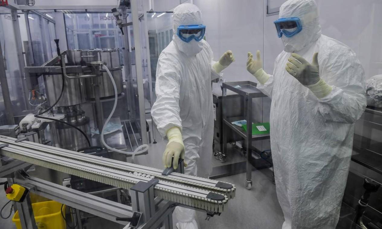 Funcionários trabalham sala de selagem da vacina Coronavac. Acesso ao ambiente é controlado e restrito Foto: NELSON ALMEIDA / AFP