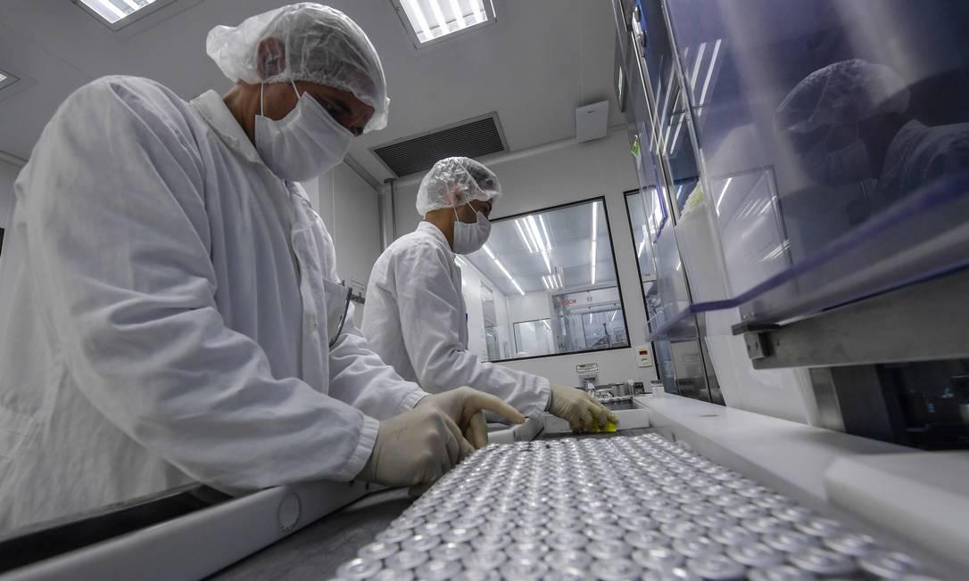 Uma vez selados, os frascos são organizados em bandejas antes do controle de qualidade Foto: NELSON ALMEIDA / AFP