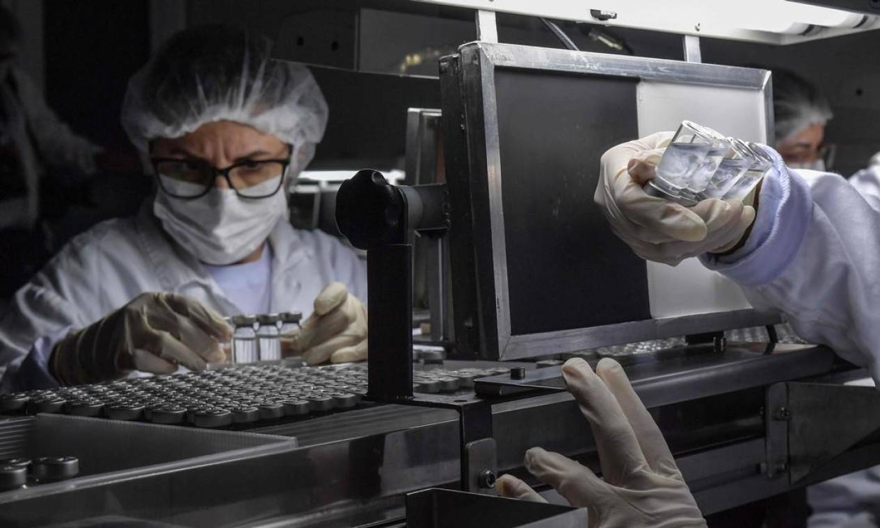 Funcionária faz inspeção visual da vacina Coronavac Foto: NELSON ALMEIDA / AFP