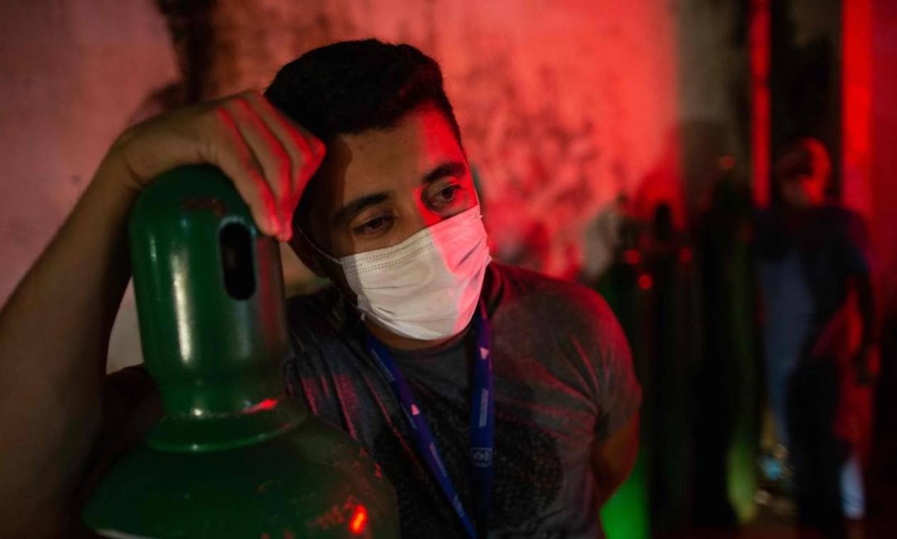 Um homem segura um tanque de oxigênio em Manaus. O sistema de saúde da capital amazonense está em colapso. Unidades de tratamento intensivo do hospital da cidade estão com 100% da capacidade nas últimas duas semanas, enquanto os profissionais da área médica lutam contra a falta de oxigênio e outros equipamentos essenciais Foto: MICHAEL DANTAS / AFP