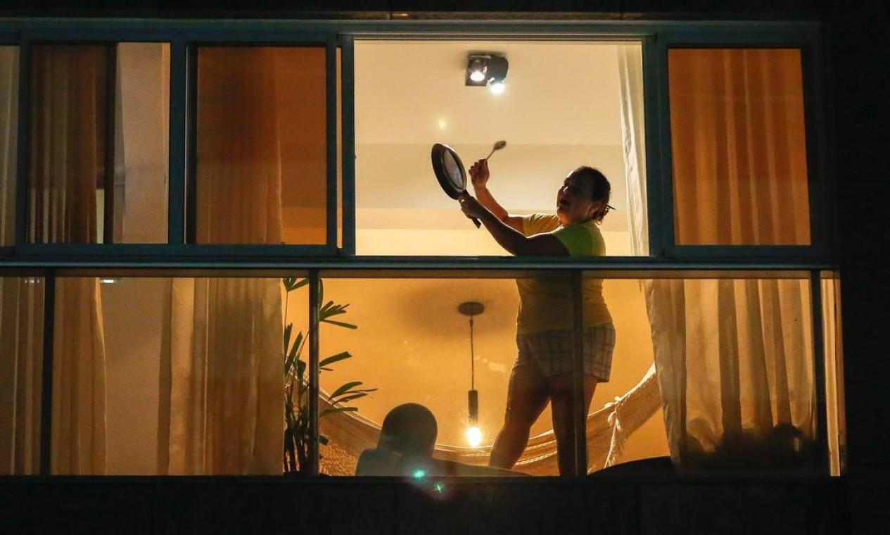 Mulher bate panelas na janela de seu apartamento, em Brasília, durante pronunciamento de Bolsonaro Bolsonaro na TV Foto: SERGIO LIMA / AFP