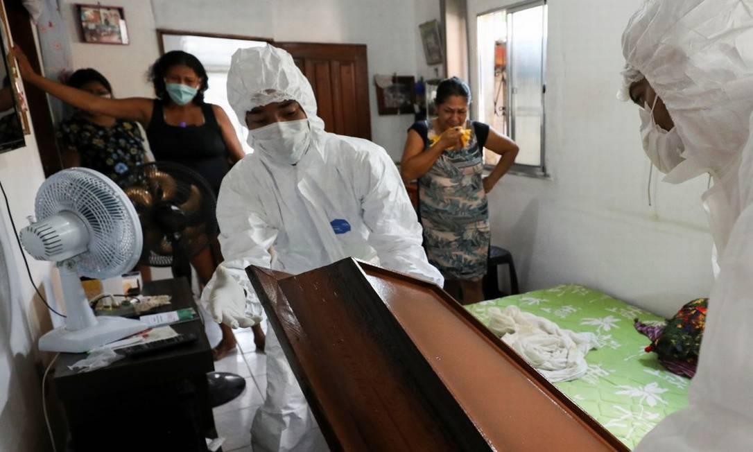 Em Manaus, trabalhadores funerários removem o corpo de Adamor Mendonça, que morreu em casa de Covid-19 após não conseguir uma vaga no hospital em meio à crise sanitária no Amazonas Foto: BRUNO KELLY / REUTERS
