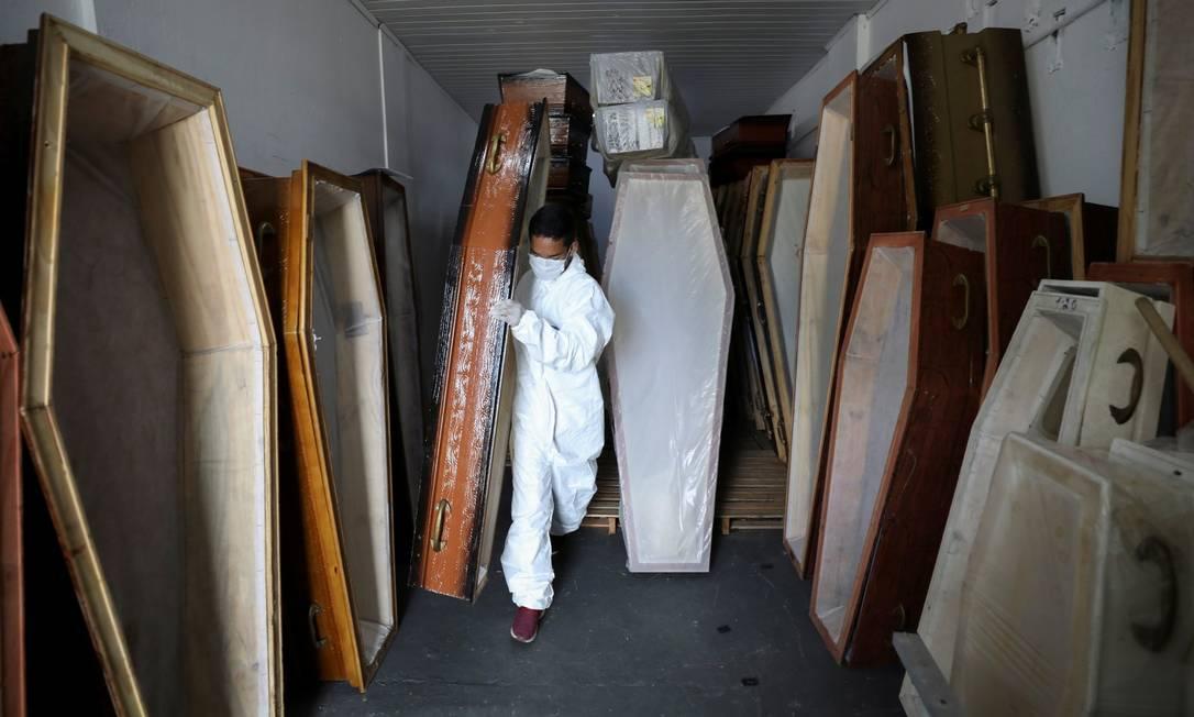 Com roupas de proteção, funcionário da SOS Funeral carrega caixão para vítima da Covid-19 Foto: BRUNO KELLY / REUTERS