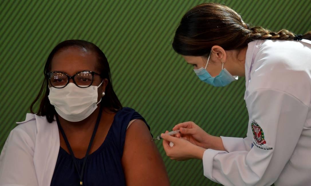 A enfermeira Mônica Calazansis foi a primeira brasileira a receber a vacina contra Covid-19, na tarde deste domingo, no Hospital das Clínicas, em São Paulo. Campanha nacional começa, segundo Ministério da Saúde, na próxima quarta-feira. Governo de São Paulo deu pontapé inicial neste domingo, com imunização de profissionais de saúde que trabalham na linha de frente de enfrentamento à doença Foto: NELSON ALMEIDA / AFP - 17/01/2021