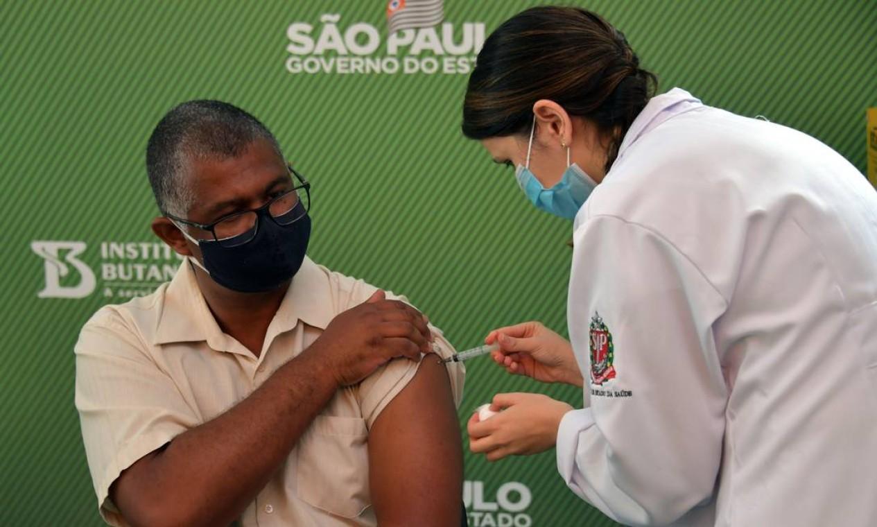 Enfermeiro Crustiano Francisco é inoculado com a vacina CoronaVac Sinovac Biotech, em São Paulo. Início da imunização de brasileiros acontece no mesmo dia em que a Anvisa autorizou o uso emergencial das vacinas CoronaVac, produzida em parceria entre o Butantan e farmacêutica chinesa Sinovac, e a do laboratório anglo-sueco AstraZeneca, desenvolvida em parceria com a Universidade de Oxford Foto: NELSON ALMEIDA / AFP