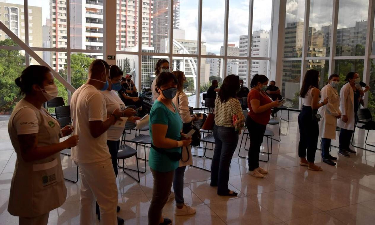 Profissionais de saúde fazem fila para receber a primeira dose da vacina CoronaVac no Hospital das Clínicas, em São Paulo Foto: NELSON ALMEIDA / AFP