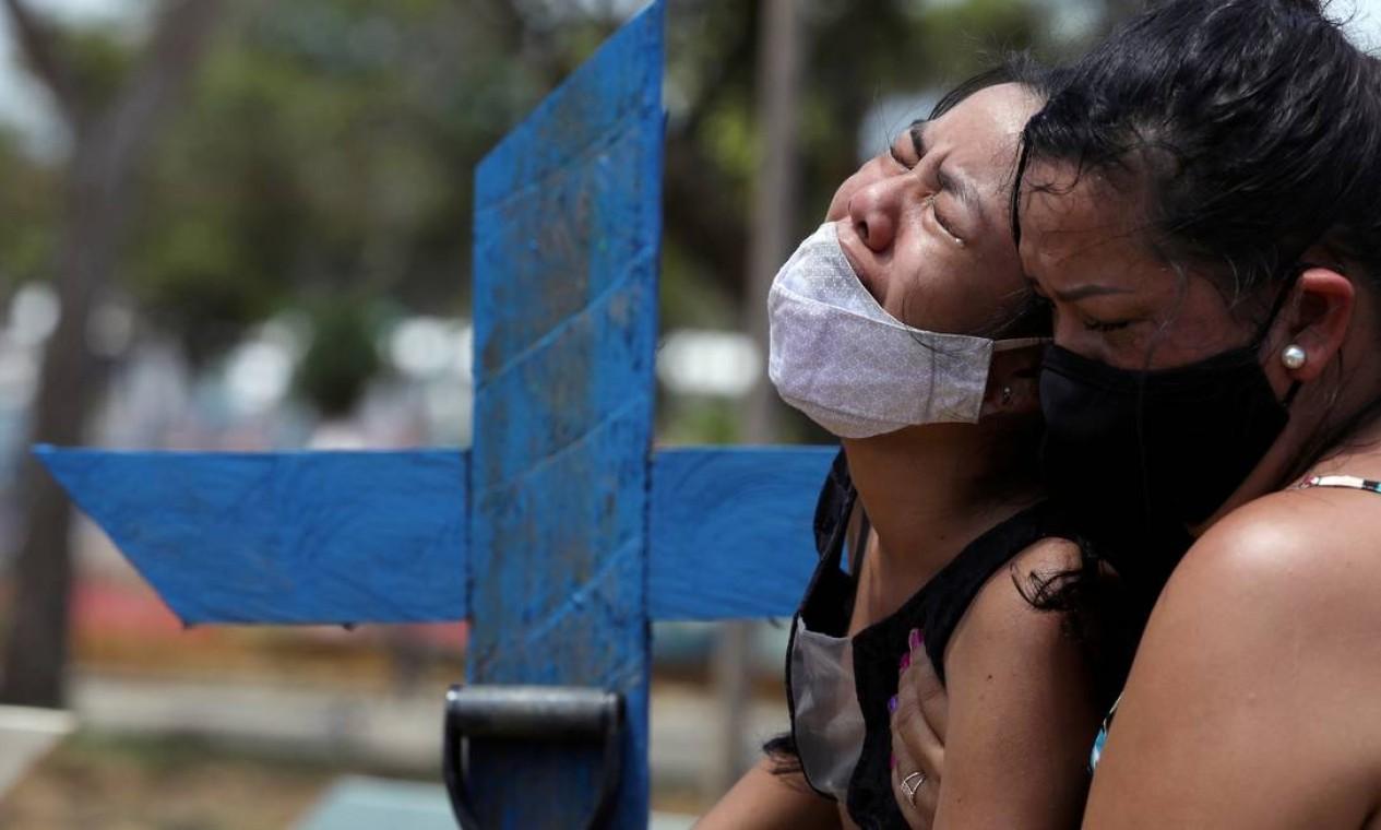 Kelvia Andrea Goncalves, 16, é amparada pela tia Vanderleia dos Reis Brasão, 37, durante o sepultamento de sua mãe Andrea dos Reis Brasão, 39, vítima do coronavírus, no cemitério Parque Tarumã, em Manaus Foto: BRUNO KELLY / REUTERS