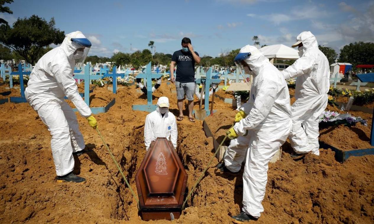 Alexandro Pinheiro Martins, 32 anos, acompanha enterro de sua irmã Elissandra Pinheiro, 39 anos, e sua sobrinha Maria Ketheleen, 22, ambas vítimas da doença, no cemitério do Parque Tarumã, em Manaus Foto: BRUNO KELLY / REUTERS